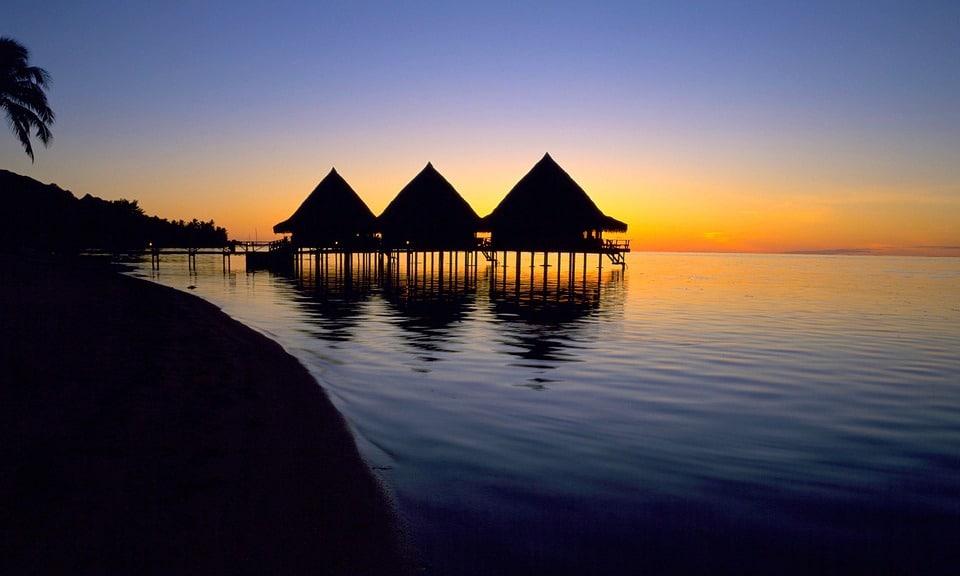 Coucher de soleil et cabanes dans l'eau à Tahiti